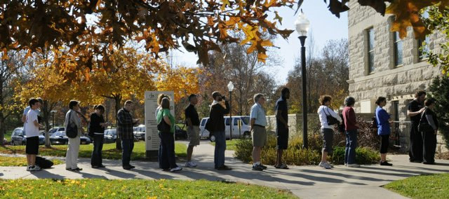 A long line of voters waits outside the Douglas County Courthouse to cast their ballots Monday on the last day of advance voting. County officials estimated that the wait would be about 30 minutes because of the number of voters. Some people in line passed the time by crocheting, e-mailing, reading or photographing the scene.