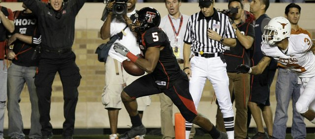 Texas Tech receiver Michael Crabtree (5) scores the winning touchdown in front of Texas defender Curtis Brown (3) on Saturday in Lubbock, Texas. The last-second victory was one of the many miraculous Red Raider comebacks in the Mike Leach era.