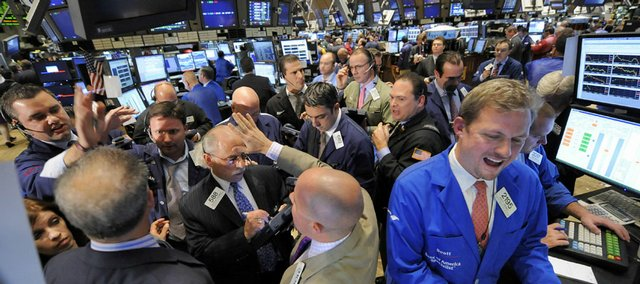 Traders gather Wednesday at a post on the floor of the New York Stock Exchange. Volatility has returned to Wall Street, with the Dow Jones industrials falling 486 points to 9,139 on Wednesday. All the major indexes slid more than 5 percent.