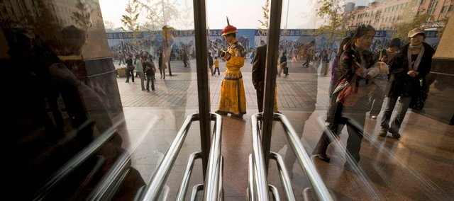 A man dressed up to look like a Chinese emperor as a publicity gimmick to draw in shoppers stands Monday outside a mall in Beijing. China announced a $586 billion stimulus package Sunday to boost government spending on roads, airports and other infrastructure as well as bigger subsidies to the poor and farmers.