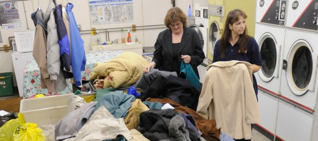 Shelly Wright, Scotch Fabric Care Services store supervisor, top left, and Laurie Clark, general manager, look through a pile of coats donated for the annual Scotch Share the Warmth project. Donated coats can be dropped off through Nov. 26 at any of the seven Scotch Fabric Care Services stores. The Salvation Army will handle the distribution of the coats Dec. 5 and 6. Clark estimates that between 1,200 and 1,500 coats have been donated so far.