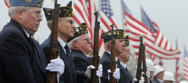 The American Legion Honor Guard salutes servicemen and servicewomen at a Tuesday ceremony at the American Legion Dorsey-Liberty Post No. 14 on West Sixth Street. The Legion celebrated Veterans Day with song, story and a gun salute, despite a light morning rain.