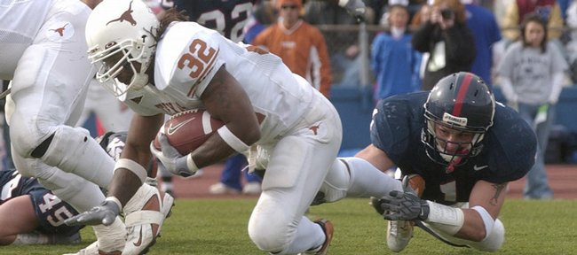 Kansas linebacker Gabriel Toomey, right, trips up Texas running back Cedric Benson in the second half of the teams' 2004 meeting in Lawrence. Though KU threw a scare into the Longhorns, the Jayhawks ultimately suffered a 27-23 loss.