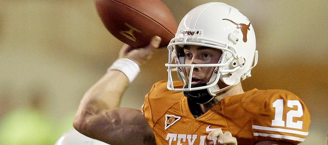 Texas quarterback Colt McCoy (12) is pursued by Missouri defender Ziggy Hood, right, during the first quarter of their NCAA football game in Austin, Texas, Saturday, Oct. 18, 2008. Texas' Charlie Tanner assists on the play.