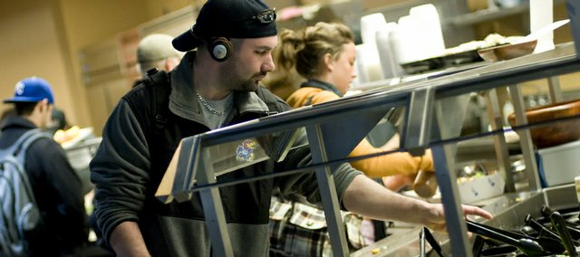 Kansas University senior Justin Litt, of Maple Grove, Minn., moves through the salad bar Monday at The Underground in Wescoe Hall. A proposal before the Kansas Board of Regents would increase the cost of housing and dining rates at the university for students living in on-campus housing.