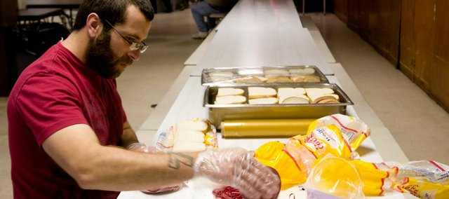 Salvation Army volunteer Arthur Elmer puts together bologna sandwiches within the food pantry area of the shelter to be given away later Friday at the Salvation Army, 946 N.H. Shelter workers explained that the demand for food and living assistance is much higher than what the shelter has to offer because of a lack of donations.