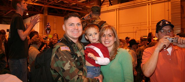 Kansas National Guard Capt. Trent Miller holds his son, Hayden, while standing with his wife, Christy. Miller will be going to Afghanistan next year with the Guard's Agribusiness Development Team.
