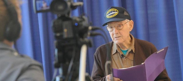 Grover Sanders, Lawrence, records a message for troops overseas Saturday at Crown Automotive, 3400 Iowa. Sunflower Broadband's Channel 6 camera crews were on hand to videotape messages to send to troops in Iraq and Afghanistan. People were also invited to drop off items to be sent to troops.