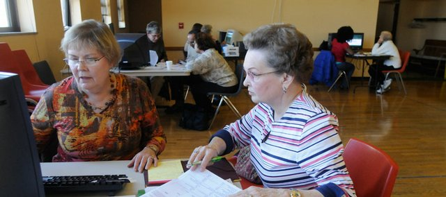 In this 2008 file photo, Sally Brandt, left, a volunteer with the Senior Health Insurance Counseling for Kansas, helps Glenda Brenton with Medicare Part D enrollment paperwork at the Lawrence Senior Center, 745 Vt.