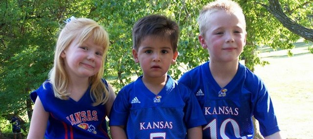 Young Jayhawk fans wait to cheer KU to its first 2008 home game victory. From left are Zoie Ecord, Mateo Marrara and Kael Ecord.