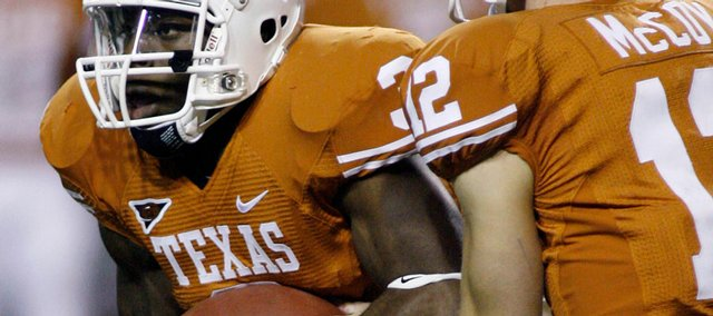 Texas running back Chris Ogbonnaya, left, takes a handoff from quarterback Colt McCoy. Texas defeated Texas A&M, 49-9, on Thursday night in Austin, Texas.
