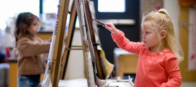 Three-year-old Caroline Scarbrough, right, touches up a masterpiece during a recent preschool class at the Lawrence Arts Center, 940 N.H. It's difficult to keep track of all the artwork kids bring home — which pieces should you keep, and what's the best way to store them?
