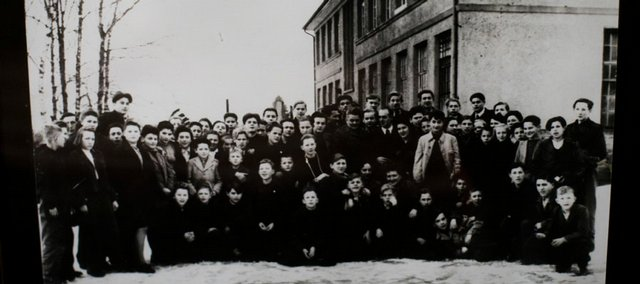 Lou Frydman, about two thirds of the way to the right, in the middle row and wearing a white coat, stands out in a group photograph made after World War II's end in Heidelberg, Germany. The picture was taken at a children's school Frydman attended for nine months in Germany following the war.