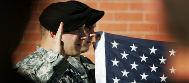 Sgt. Ryun Nyhus re-enlists during a ceremony at Fort Riley, Kan., Wednesday, Nov. 26, 2008. He spent 14 months patrolling the deadly streets of Baghdad, where five members of his platoon were shot and one died. As bad as that was, he would rather go back there than take his chances in this brutal job market.