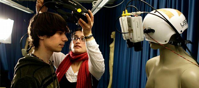Valeria Petkova, center, of the Karolinska Institute in Stockholm prepares student Andrew Ketterer to test the 'body-swap' illusion, a Swedish science project were people can experience the illusion that either a mannequin or another person's body is their own body in Stockholm, Monday Dec. 1, 2008. In a study presented Tuesday, neuroscientists at Stockholm's renowned Karolinska Institute show how they got volunteers wearing virtual reality goggles to experience the illusion of swapping bodies with a mannequin and a real person.