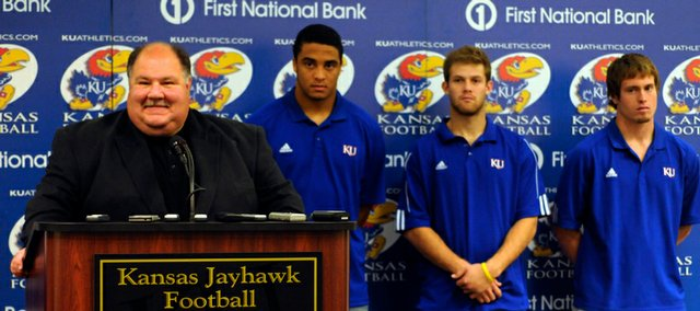 KU football coach Mark Mangino smiles during Friday's press conference where KU officially announced its plans to accept a bid into the Insight Bowl. Behind him are players, from left, James Holt, Todd Reesing and Jake Sharp.
