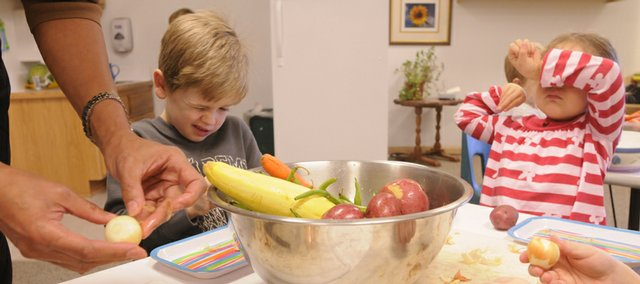 Raintree Montessori School students, from left, Reese Gray, 5, and Isley Newton, 4, tear up while trying to peel some onions for a Thanksgiving meal.
