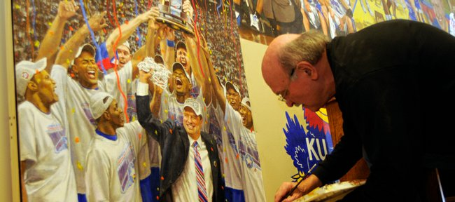 Portrait artist John Martin, a Kansas University graduate who lives in Mission, touches up the mural inside KU's men's basketball office on Monday. Martin started the mural 29 years ago, and his latest addition commemorates KU's national championship last season.