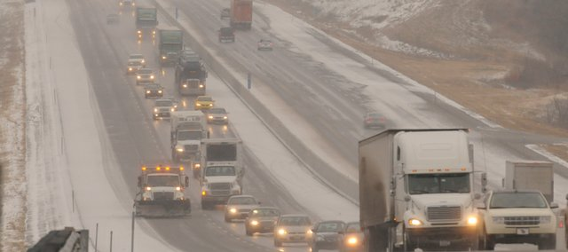 A long line of cars and trucks back up after a minor accident west of Lawrence Tuesday backed up traffic. A Kansas Turnpike snowplow moves down the left-hand lane in an effort to keep more motorists from suffering the same fate.