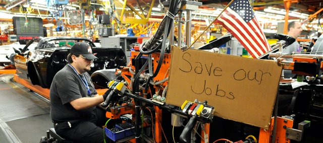 Mark Madden, a General Motors Corvette assembly plant worker, hangs a door on a Corvette on Friday at the Bowling Green, Ky., facility. Madden put a sign up at his work station when talks about helping the ailing auto industry began to fail.