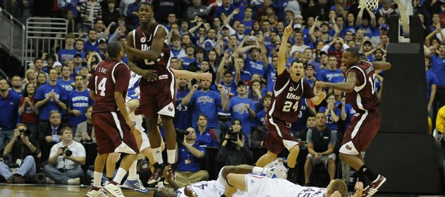 Kansas players Sherron Collins, left, and Cole Aldrich watch from the floor at the buzzer as UMass players celebrate their 61-60 win over the Jayhawks Saturday, Dec. 13, 2008 at the Sprint Center in Kansas City, Mo.