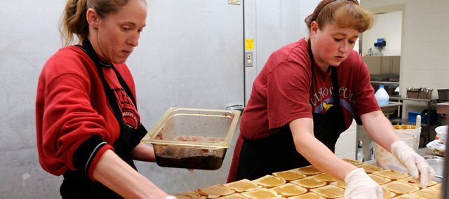 From left, Kennedy School cafeteria workers Jackie Stone and Kathy Barnes make peanut butter and jelly sandwiches Wednesday. As the economy has gotten more shaky, the number of children receiving a free lunch or reduced lunches has increased in Kansas public schools.