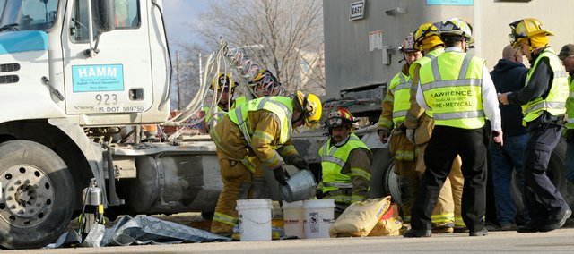 Lawrence-Douglas County Fire & Medical crews drain diesel fuel from a damaged Hamm Quarry's semi-trailer truck involved in an accident at the intersection of U.S. Highway 24-59 onto U.S. Highway 24-40.