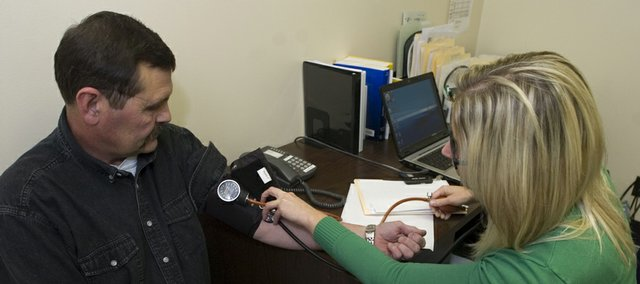 Allen Hout (left), an employee with the Lawrence Paper Company for 36-years, has his blood pressure checked by nurse practitioner Crystal Acker. The company has a wellness clinic where employees can make appointments similar to a doctor's office.