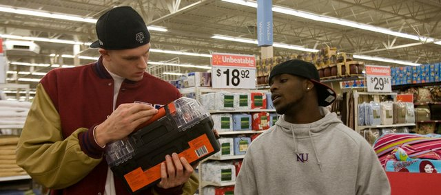 Kansas University sophomore center Cole Aldrich, left, and junior guard Sherron Collins examine the contents of a toolbox trying to decide if it is the right gift for someone on their shopping list. The KU men's basketball team spent part of Thursday night shopping at Wal-Mart for gifts for area families.