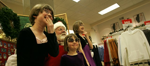 Sisters, from left, Morgan, 7, Addison, 3, and Kyleigh Leslie, 9, try to keep their composure while visiting with Santa. Larry Freeman, who has portrayed Santa Claus in the Lawrence Christmas Parade for several decades, has conducted picture sessions at Weaver's, 901 Mass., every year for at least the past 10 years.