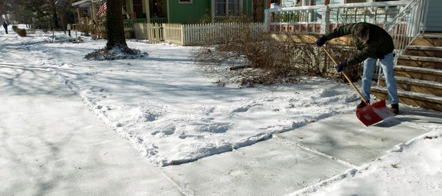 A Lawrence resident clears the snow from his sidewalk in front of his home in this 2008 photo.