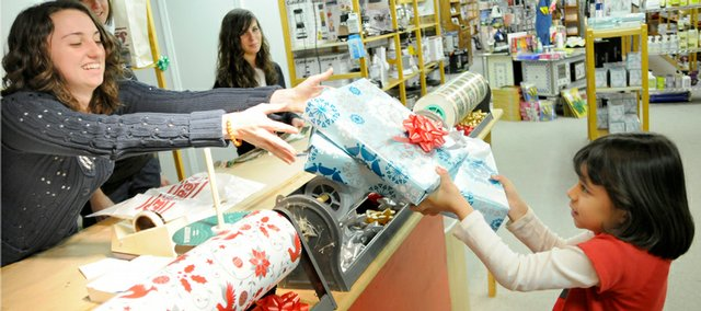Paula Kyriakos, left, Lawrence, hands Nola Levings, 6, right, Lawrence, her Christmas gifts Tuesday at Weaver's Department Store, 901 Mass. Levings' gifts were for her grandfather and she was picking them up from Kyriakos, who was wrapping customers' gifts with a couple of other employees at the downtown department store. In the background at top left are gift wrappers Megan Ballock, Eudora, and Samantha Otte, Lawrence.