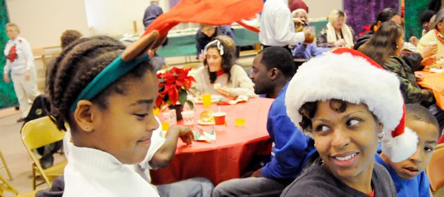 Sanders Barbee, 8, left, wears reindeer antlers while her mother, Kim Barbee, sports a Santa hat as their family enjoys Lawrence's Free Community Christmas Dinner on Thursday at the First United Methodist Church. At far right is Kim's son John Barbee II. Kim's husband and the children's father, John Barbee, is serving in Kuwait and this is the first Christmas he hasn't been home. The family volunteered at the meal site Thursday.
