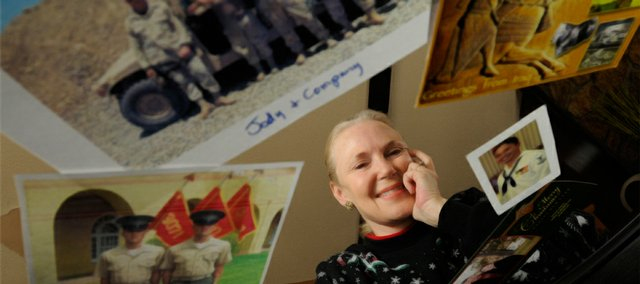 Lawrence resident Vicki Brown is pictured with several of the photographs and post cards she has received from soldiers serving in Iraq and Afghanistan. Since 2003 Brown has sent over 100 care boxes to soldiers with items ranging from socks to squirt guns.