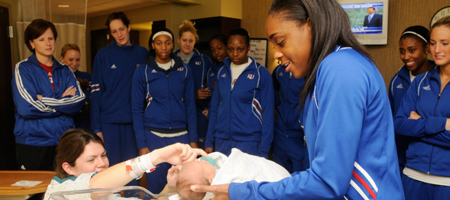 Kansas University women's basketball player LaChelda Jacobs holds newborn Annie Serafine, daughter of Bradley and Mandy Serafine, of Lawrence, Monday at Lawrence Memorial Hospital. as the rest of the team looks on. The basketball team made its annual visit to the hospital, bringing gifts to patients, including in the Family Birthing Center.