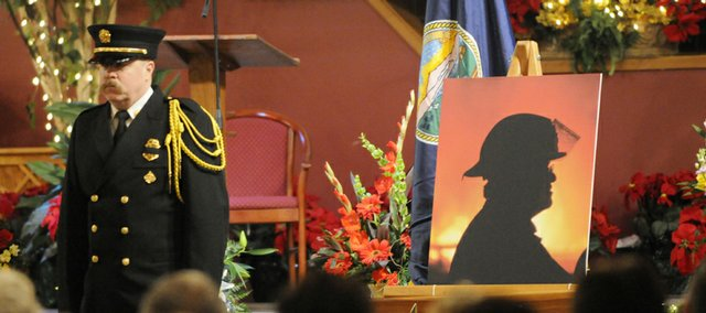 Honor guard Jim Thornton, a firefighter at Station No. 5, left, stands at attention next to a photograph of former Lawrence-Douglas County Fire Chief James McSwain, during a memorial service for McSwain Tuesday at Mustard Seed Church. McSwain died Thursday, Dec. 25.