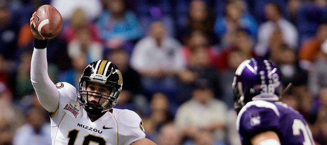 Missouri QB Chase Daniel scrambles as he is pursued by Northwestern's Brian Peters.