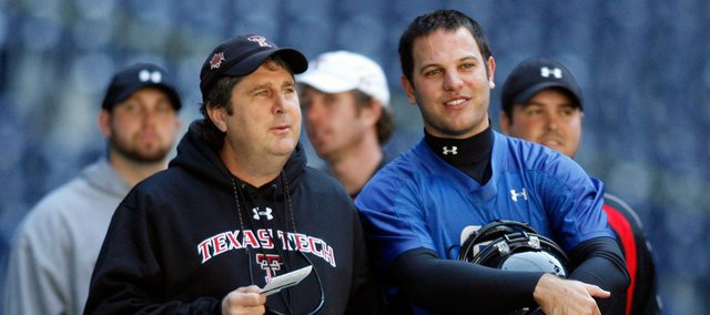 Texas Tech coach Mike Leach, left, and quarterback Graham Harrell talk during practice as the team prepares for the Cotton Bowl. Tech will face Mississippi on Friday in Dallas