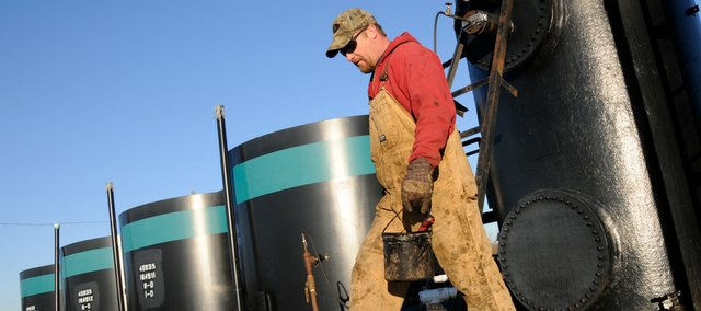 David Ericson checks an oil tank battery this week east of Vinland. Ericson makes daily rounds inspecting dozens of area oil wells and tanks for Colt Energy. The number of new oil wells drilled in Kansas in 2008 dropped off. Colt hasn't shut down any producing wells, but it is slowing future drilling.