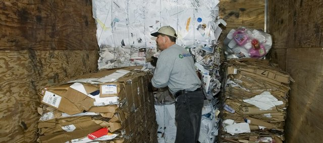 Tom Boxberger checks bundles of cardboard after they were loaded onto a trailer Friday at the KU recycling center.