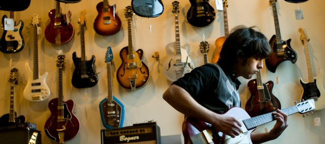 Kansas University junior Zach Shoffner tests an electric guitar before a wall of musical merchandise Thursday at Mass. Street Music, 1347 Mass. Sales tax revenue for the city of Lawrence was up 3.8 percent for 2008.