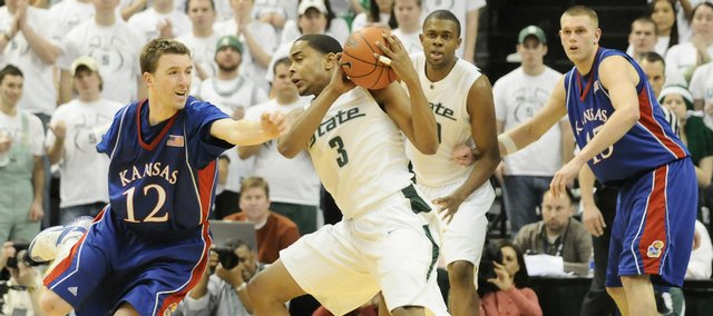 Kansas guard Brady Morningstar fails to swipe away the ball from Michigan State guard Chris Allen during the second half Saturday, Jan. 10, 2009 at the Breslin Center in East Lansing, Michigan.