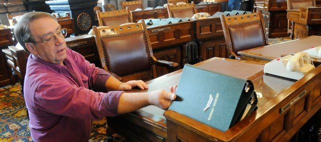George Sommers, an assistant Sergeant of Arms in the Senate at the Statehouse in Topeka, sets out notebooks for legislators Wednesday, Jan. 7, 2009. Sommers and other state employees were making preparations for Monday's State of the State address and the opening of the legislative session for 2009.