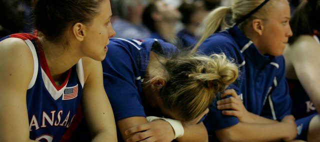 Kansas guard Katie Smith (middle) can't stand to watch while teammates Ivana Catic (left) and Kelly Kohn look on as Kansas State extends their lead over the Jayhawks in the second half of the game Saturday night in Manhattan, Kan.