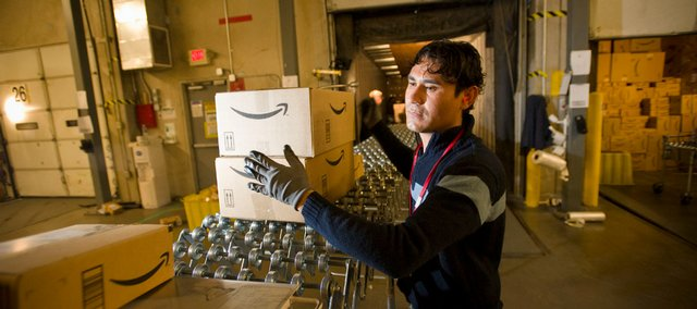 An Amazon.com employee grabs boxes to be loaded onto a truck at the company's Fernley, Nev., warehouse in this Dec. 1, 2008, file photo. States are increasingly looking to collect taxes from online retail sales as a way to fill gaps in budgets.