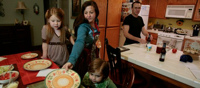 Cindy Reilly, center, sets the dinner table for her children Isabella, 7, left, and Sierra, 4, and her husband, Mike, last week in the kitchen of their home in Nipomo, Calif. The family has decided to escape California's high cost of living by moving to Colorado in February.