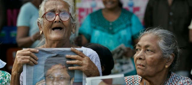 Sri Lankan women hold a photograph of newspaper editor Lasantha Wickrematunge during his funeral procession Monday in Colombo, Sri Lanka.