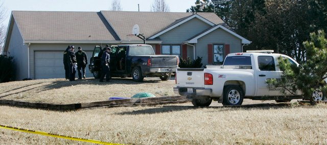 Osage County Sheriff's and Scranton Police officers meet outside a home in Scranton on Tuesday. An adult and three children were found dead at the house on Monday, and a fire that had been set inside was ruled arson.