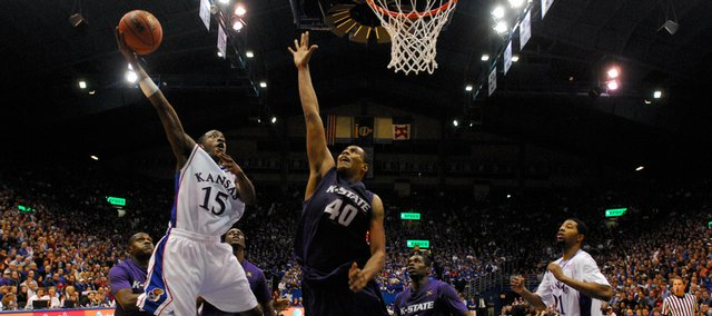 Kansas guard Tyshawn Taylor hooks a shot around Kansas State forward Ron Anderson during the second half Tuesday, Jan. 13, 2009 at Allen Fieldhouse.