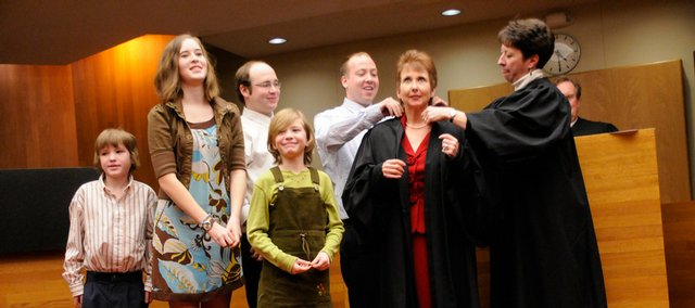 Sally Pokorny, second from right, is fitted with her robe by her son Brian, at left and Shawnee County District Judge Jean Schmidt, right.  Pokorny was sworn in as the newest Douglas County District Court judge Thursday, Jan. 15, 2009. Also joining Pokorny for her robing ceremony from left are Deke Davis, 11, Ellie Davis, 13, Pokorny's son Mike, and Libby Davis, 7. The Davis's are nephews and nieces of Pokorny.